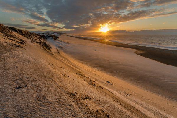 Sonnenaufgang am schwarzen Strand